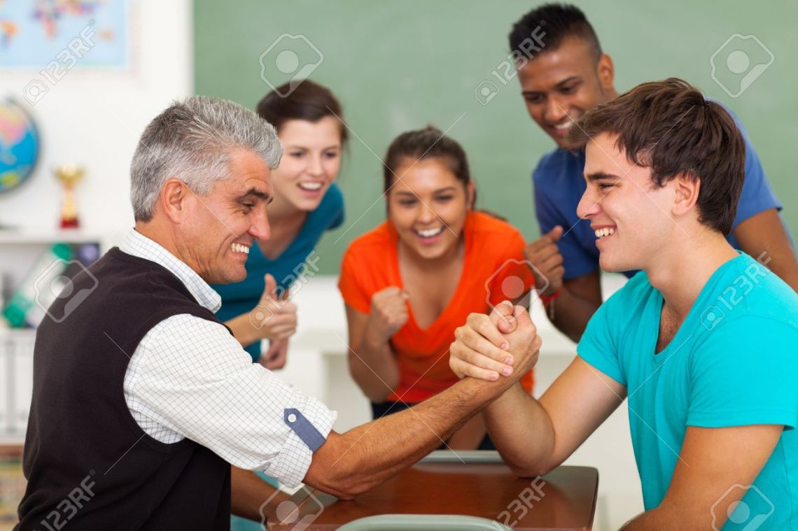 20235274-friendly-middle-aged-teacher-arm-wrestling-with-high-school-student-in-classroom-during-break-Stock-Photo.jpg